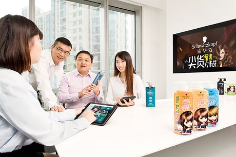 Asian employees are sitting at a table talking about Beauty Care products.