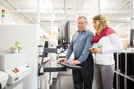 Male and female employee are looking at a computer at a production line.